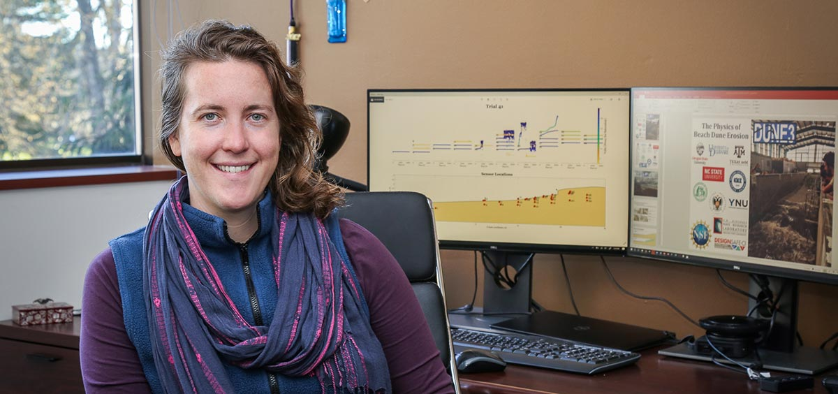 Meagan Wengrove at her desk in front of her research on computer screens.
