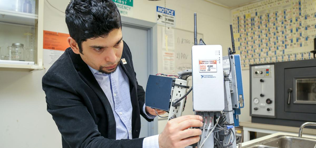 Erdem Coleri examines a testing device in his lab.