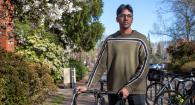 Graduate student Cadell Chand stands with his bicycle next to Owen Hall.