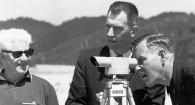 Historical image of three people on a beach with surveying equipment.